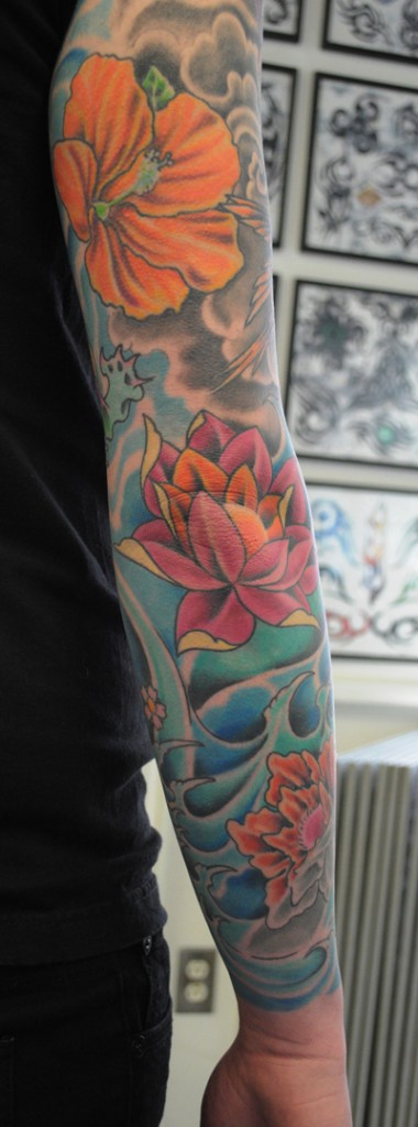 sleeve tattoo comprised of flowers, birds and a frog