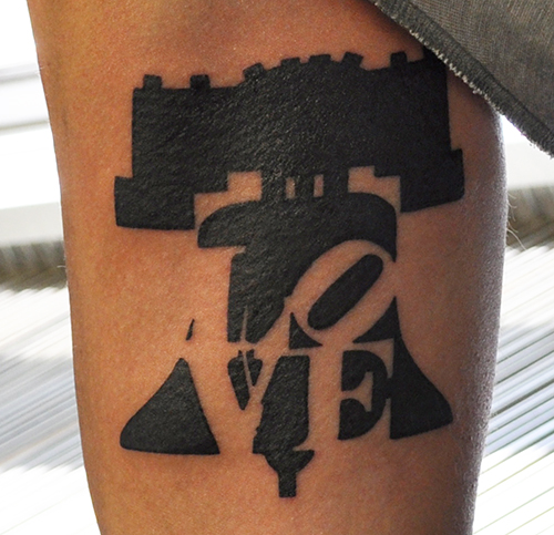 Liberty Bell Tattoo on the inside bicep with the love park statue in negative space